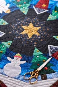 Detail of a Christmas quilt with scissors