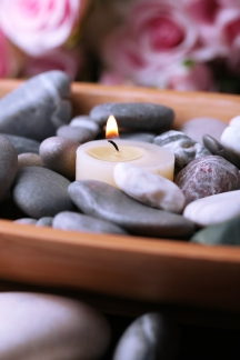 Wooden bowl with spa stones and candles on wooden  table, on flowers background